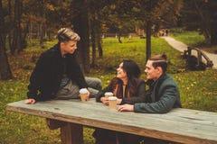 Amis derrière la table en bois en parc d'automne Images stock