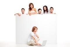 Amis derrière le panneau blanc et l'ordinateur portatif Image stock