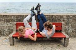 Amis des jeunes détendant sur le banc Photo stock