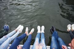 Amis des jeunes s'asseyant sur le pont de rivière, mode de vie, pieds au-dessus de l'eau bleue Images stock