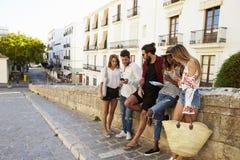 Amis des vacances dans Ibiza regardant le guide et le téléphone Photographie stock