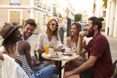 Amis des vacances riant en dehors d'un café dans Ibiza Images stock