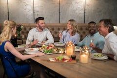 Amis dinant ensemble dans le restaurant Images stock