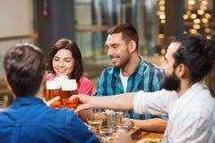Amis dinant et buvant de la bière au restaurant Image libre de droits