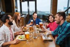 Amis dinant et buvant de la bière au restaurant Image stock
