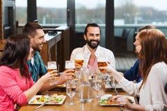 Amis dinant et buvant de la bière au restaurant Photos libres de droits