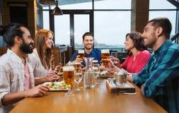Amis dinant et buvant de la bière au restaurant Photographie stock libre de droits