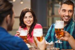 Amis dinant et buvant de la bière au restaurant Photographie stock