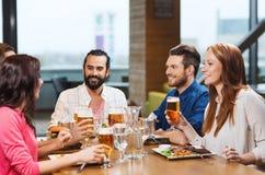 Amis dinant et buvant de la bière au restaurant Photo stock