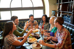 Amis dinant et buvant de la bière au restaurant Images stock
