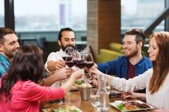 Amis dinant et buvant du vin au restaurant Image stock