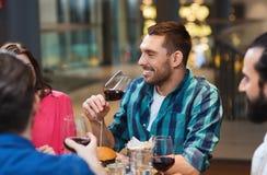 Amis dinant et buvant du vin au restaurant Photo stock