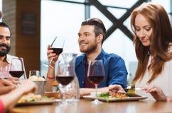 Amis dinant et buvant du vin au restaurant Photos stock
