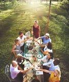 Amis dinant le concept extérieur de jardin de nature Image libre de droits