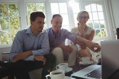 Amis discutant au-dessus de l'ordinateur portable Images libres de droits