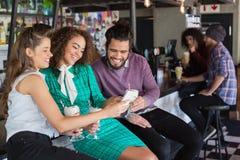 Amis discutant au-dessus du mobile tout en ayant la boisson dans le restaurant Image libre de droits