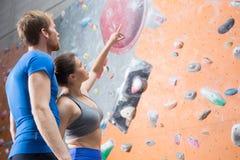 Amis discutant en escaladant le mur dans le gymnase de crossfit Images stock
