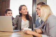 Amis discutant et se dirigeant sur l'écran d'ordinateur portable Image stock