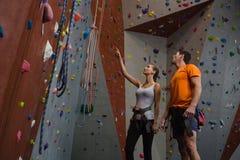 Amis discutant tout en se tenant prêt le mur s'élevant au gymnase Image stock