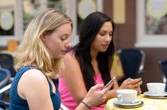 Amis distraits textotant tandis qu'assis en café Photos libres de droits