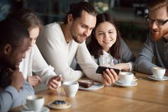 Amis divers ayant l'amusement utilisant des smartphones s'accordant dedans Images libres de droits