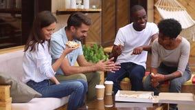 Amis divers gais s'asseyant mangeant de la pizza dans la terrasse de café d'été banque de vidéos