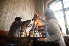 Amis divers heureux donnant la haute cinq refroidissant en café photographie stock