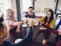 Amis divers heureux encourageant avec du café Image libre de droits