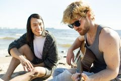 Amis divers jouant la guitare sur la plage Photographie stock