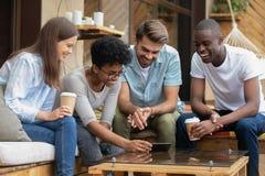 Amis divers observant la vidéo mobile drôle sur le smartphone en café images libres de droits