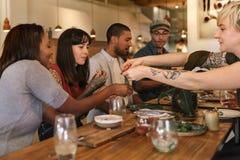 Amis divers partageant la nourriture délicieuse ensemble dans un Bistro Photographie stock libre de droits