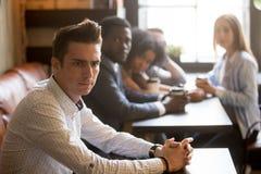 Amis divers regardant l'homme frustrant seul s'asseyant en café Images stock