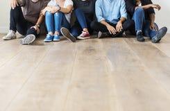 Amis divers s'asseyant ensemble sur le plancher en bois Image stock