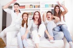 Amis divisés observant le jeu encourager pour différentes équipes Photos libres de droits