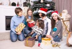 Amis donnant des présents à l'arbre de Noël Photographie stock libre de droits
