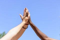 Amis donnant la haute cinq entre eux contre le ciel bleu Images libres de droits