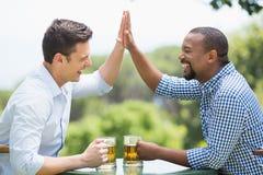 Amis donnant la haute cinq entre eux tout en ayant la bière Image stock