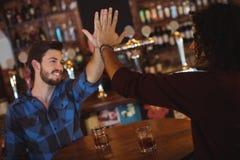 Amis donnant la haute cinq tout en ayant la boisson Photographie stock libre de droits