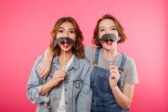 Amis drôles de femmes tenant la fausse moustache Images libres de droits
