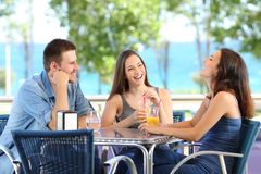 Amis drôles parlant et riant dans une barre ou un hôtel image stock