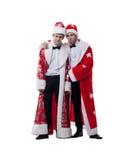 Amis drôles posant dans des manteaux de Santa Claus Images stock