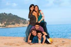 Amis effectuant la pile humaine sur la plage. Photographie stock