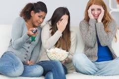 Amis effrayés avec la cuvette à télécommande et de maïs éclaté sur le sofa Photo libre de droits