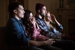 Amis effrayés observant le film avec le maïs éclaté à la maison Photo stock