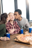 Amis embrassant les joues de sourire du ` s d'adolescente, mangeant le concept de pizza à la maison Image libre de droits