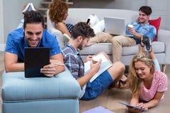 Amis employant des technologies modernes dans le salon Image stock