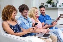 Amis employant des technologies sur le sofa Photo libre de droits