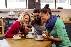 Amis employant se reposer de smartphones Image libre de droits