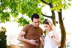 Amis en café se tenant et dactylographiant à leurs téléphones photos libres de droits