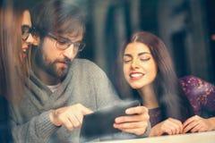 Amis en café utilisant la technologie Photographie stock libre de droits